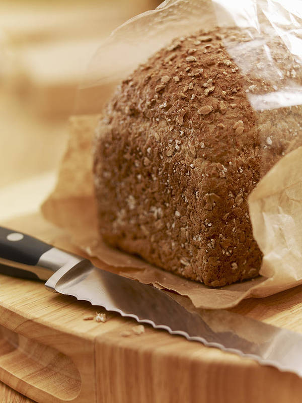 Vertical Poster featuring the photograph Close Up Of Knife And Loaf Of Bread In Wrapper by Adam Gault