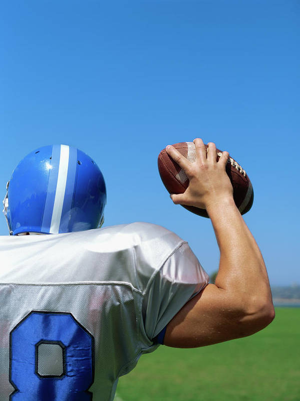 Adult Poster featuring the photograph Rear View Of A Football Player Throwing A Football by Stockbyte