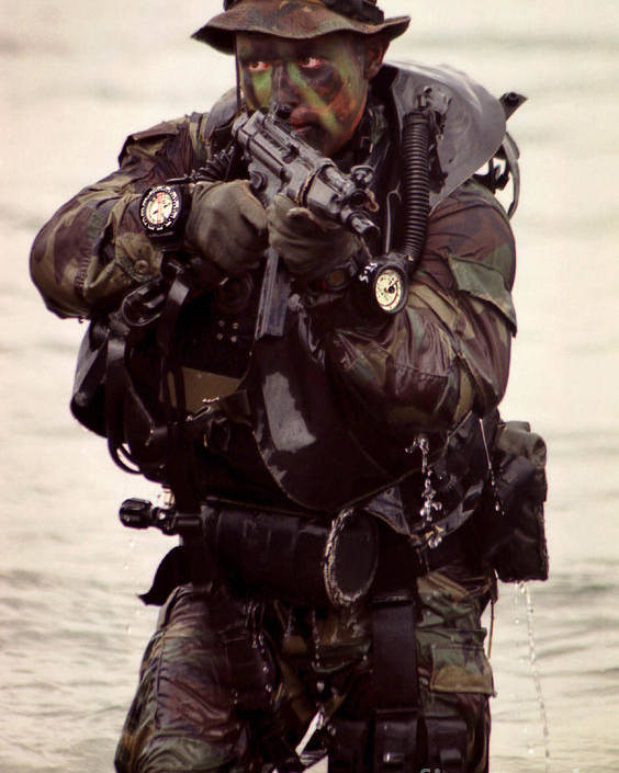 Military Poster featuring the photograph A Navy Seal Exits The Water Armed by Michael Wood