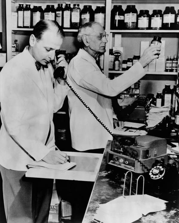 History Poster featuring the photograph A Pharmacist Demonstrates The Use Of An by Everett