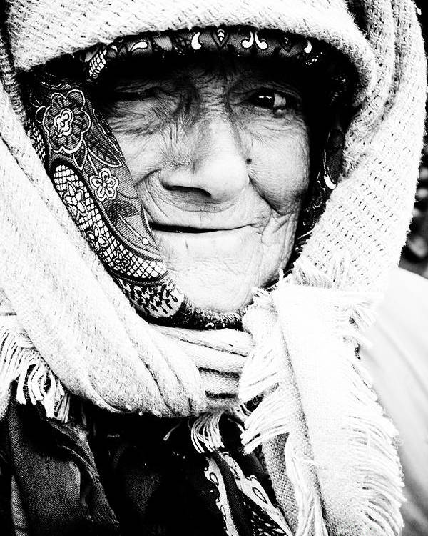 Portrait; Old; Senior; People; Female; Person; Woman; Mature; Adult; Elderly; Pensioner; Expression; Retirement; Retired; Grandmother; Face; Caucasian; Smile; White; Aged; Background; Grey; Look; Older; Wrinkle; Wrinkled; Lifestyle; Poor; Poverty; Black And White; Bw; Poster featuring the photograph Keeping Warm by Gabriela Insuratelu