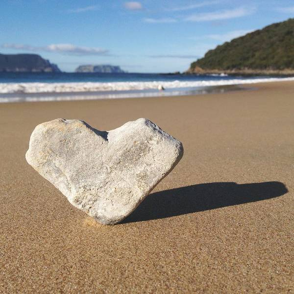 Water's Edge Poster featuring the photograph Heart Shaped Rock Sitting In Sand At by Jodie Griggs