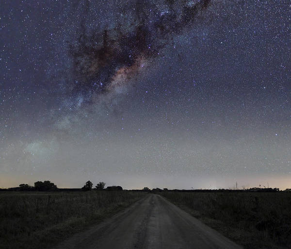 Road Poster featuring the photograph The Milky Way Galaxy Over A Rural Road by Luis Argerich