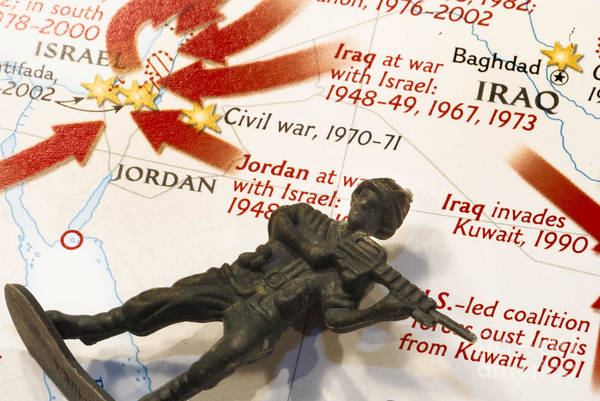 Aggression Art Print featuring the photograph Army Man Lying On Middle East Conflicts Map by Amy Cicconi