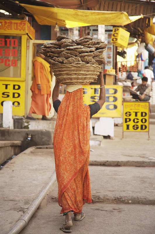 Vertical Art Print featuring the photograph Woman Carrying Cow Dung In Basket On by Paul Miles