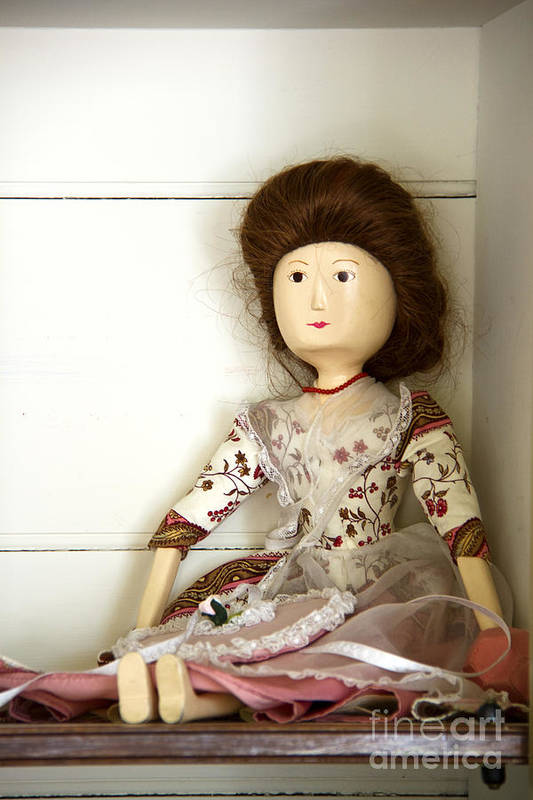 Doll; Toy; Wood; Wooden; Painted; Hair; Gentry; Colonial; Caucasian; Sit; Sitting; Shelf; Pretty; Brunette; Beautiful; Feminine; Dress; Necklace; Stare; Staring; Tiny; Female; Woman; Lady; Store; Toy Room Art Print featuring the photograph Wooden Doll by Margie Hurwich
