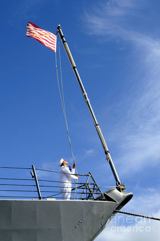 Pearl Harbor Art Print featuring the photograph A Sailor Lowers The U.s. Navy Jack by Stocktrek Images