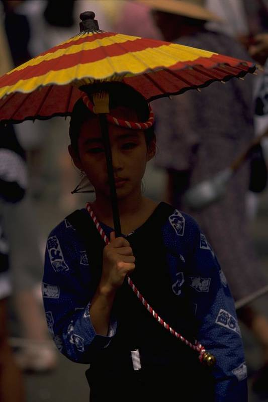 Japanese Girl In Kumamoto Traditional Dress During A Festival Japan From Nomadic Gathering The Citizen Of Celebrate Zuibyo Fujisaki Hachiman Shrine Street Procession Continue All Day And Child After Sunset Children Parade Their Colour Twirl Parasol Waft Fan Colourful Pageant Attractive Young Woman Shyly Smile Behind Photo By Michel Guntern Travelnotes Travel Er Pics Travelpics Asia Festivals Kyushu Custom Umbrella Blue Vertical Orientation Asian Portrait Cute Carnival Red Yellow Little Small Shy Art Print featuring the photograph Japanese Girl by Travel Pics