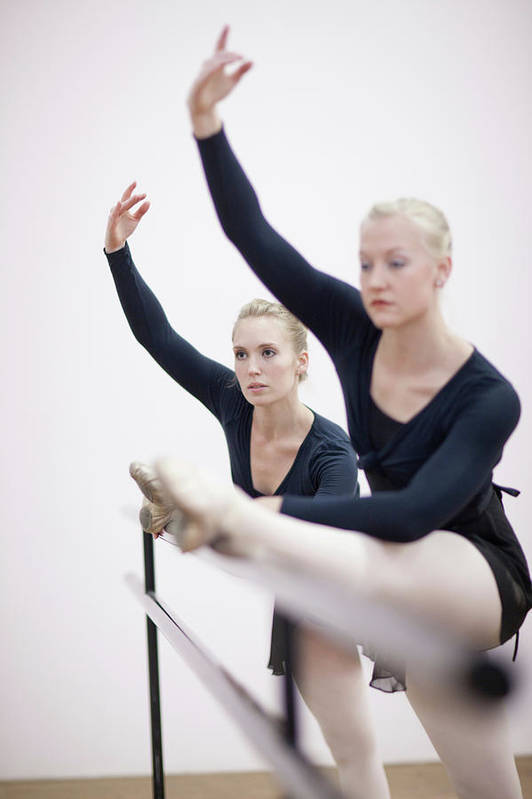 Ballet Dancer Art Print featuring the photograph Female Ballerinas Stretching At The by Zero Creatives