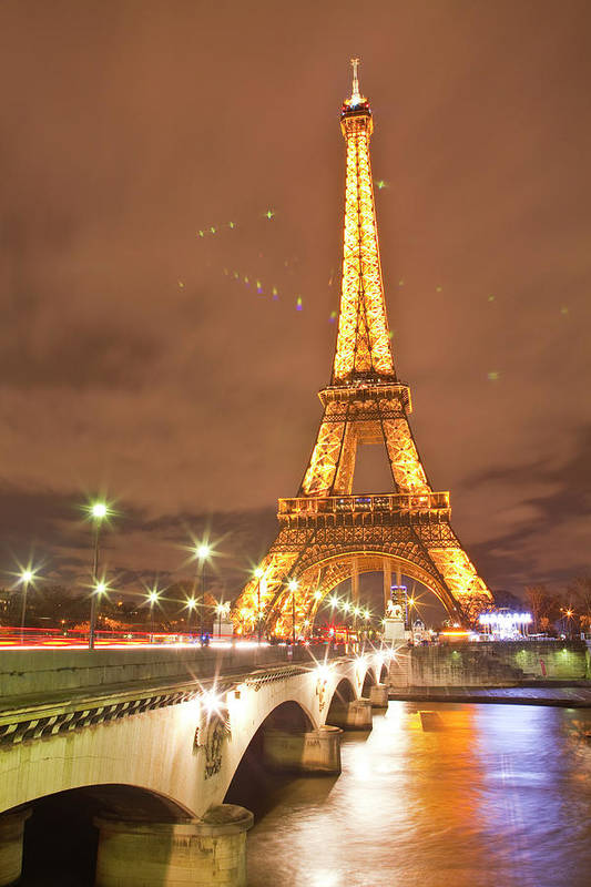 In A Row Art Print featuring the photograph The Eiffel Tower Lit Up At Night In by Julian Elliott Photography