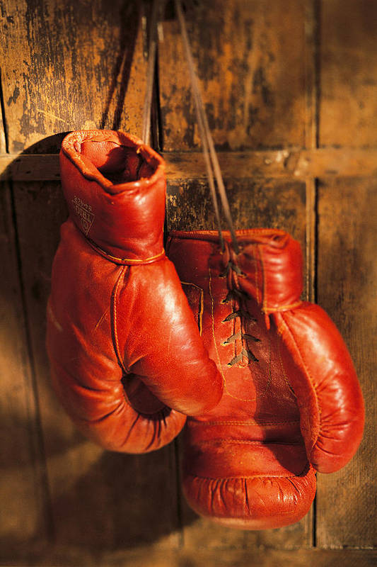 Hanging Art Print featuring the photograph Boxing Gloves Hanging On Rustic Wooden by Comstock
