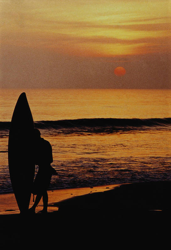 Vertical Image; Colour Image; Outdoors; Day; One Person; Unrecognisable Person; Full Length; Standing; Surfboard; Sea; Beach; Sunset; Sun; Water's Edge; Silhouette; Tranquil Scene; Leisure; Recreation; Solitude Art Print featuring the photograph Surfing At Sunset by Anonymous