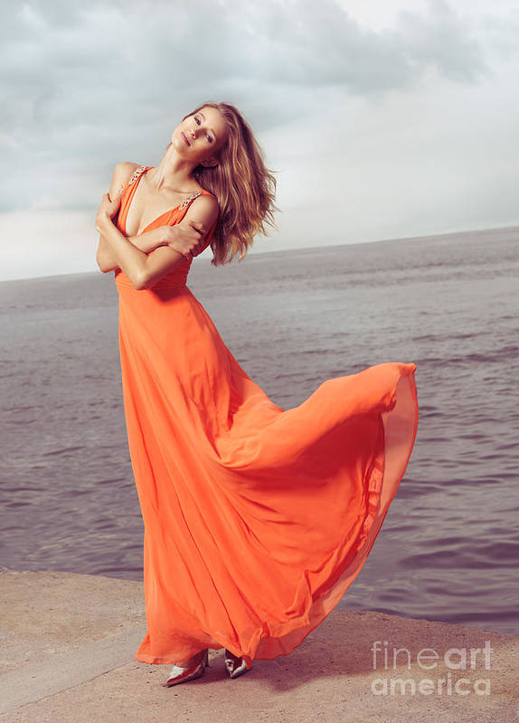 Woman Art Print featuring the photograph Young Woman In Orange Dress Flying In The Wind At Sea Shore by Oleksiy Maksymenko