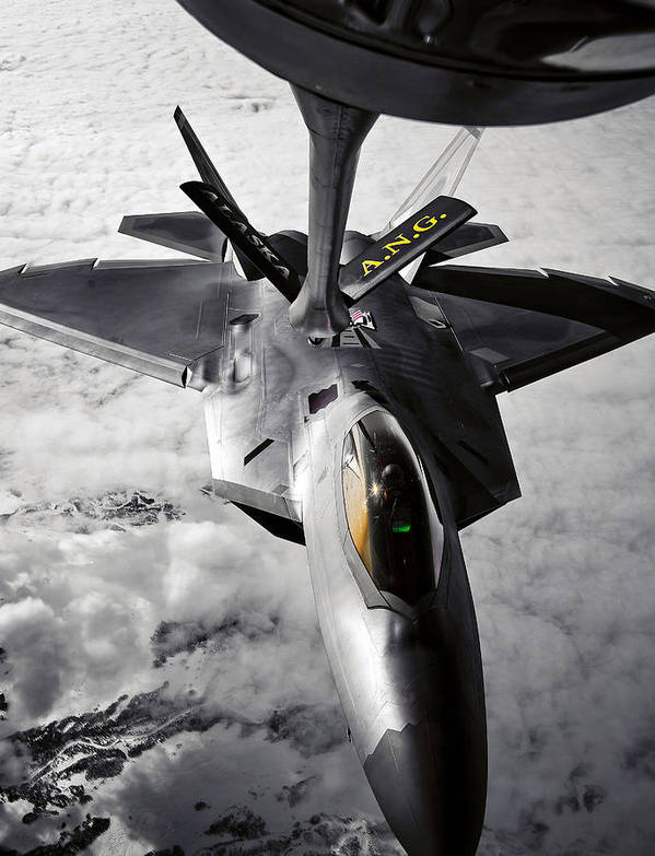 Aerial Print featuring the photograph A Kc-135 Stratotanker Refuels A F-22 by Stocktrek Images