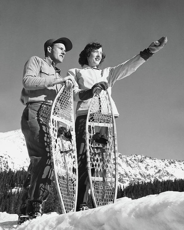 Heterosexual Couple Art Print featuring the photograph Couple Holding Snowshoes, Woman Pointing by Stockbyte