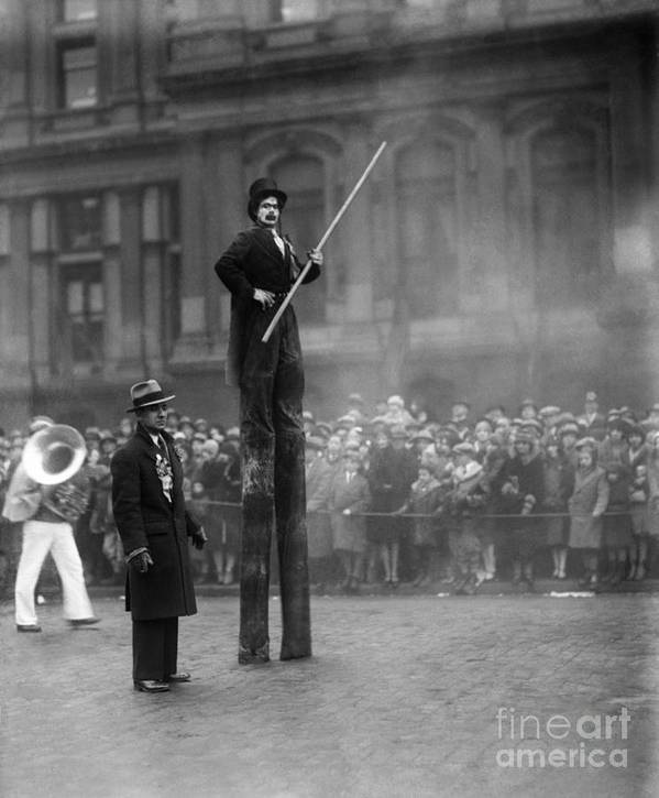 Crowd Of People Art Print featuring the photograph Performer On Stilts by Bettmann