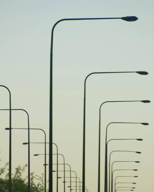 In A Row Art Print featuring the photograph Streetlights Against Afternoon Sky by By Ken Ilio