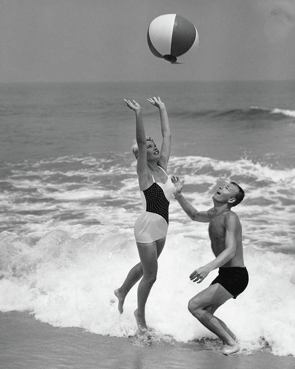 Young Men Art Print featuring the photograph Young Couple Playing With Beach Ball At by Stockbyte