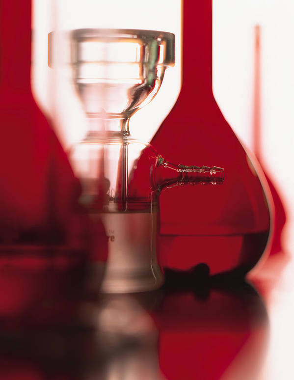 White Background Art Print featuring the photograph A Series Of Red Flasks And Beakers Stand On A Shiny Table With A White Background by Photodisc