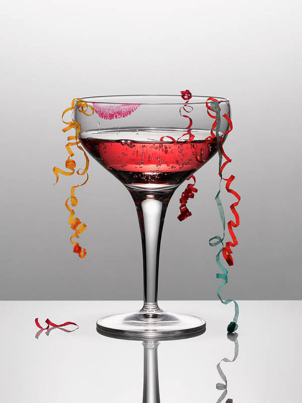 Streamer Art Print featuring the photograph Confetti Hanging From Glass Of Pink by Andy Roberts