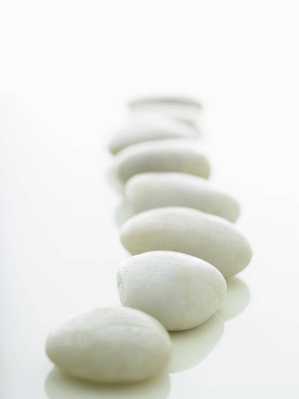 White Background Art Print featuring the photograph White Stones Lined Up On A White by Rick Lew