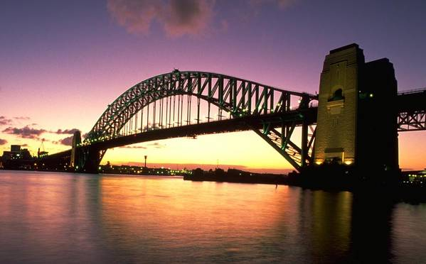 Sydney Harbour Bridge Seen At Sunset Is Classic A Symbol Of Australia The North Shore And In Down Under Wide Large Single Arch Design Span Allow Passage For Ship Photo By Michel Guntern Travelnotes Arched Over Calm Sea Against Sky Travel Er Pics Travelpics Harbor With Landmark Steel Mauve Purple Golden Water Reflection Minimum Cloud Man Made Structure Colour Dusk Horizontal No People Outdoor Tranquil Scene Landscape Nsw City Skyline Downtown Twilight Tourist Attraction Bay Tower New South Wales Art Print featuring the photograph Sydney Harbour Bridge by Travel Pics