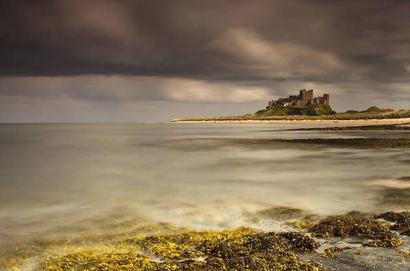 Ocean Art Print featuring the photograph Bamburgh Castle Under A Cloudy Sky by John Short