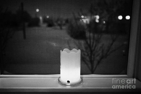 Looking Art Print featuring the photograph candle in the window looking out over snow covered scene in small rural village of Forget Saskatchew by Joe Fox
