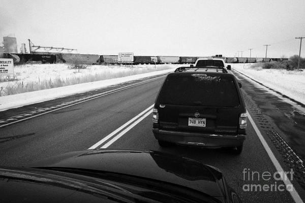 Car Art Print featuring the photograph cars waiting on train crossing trans-canada highway in winter outside Yorkton Saskatchewan Canada by Joe Fox