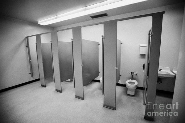 Toilet Art Print featuring the photograph cubicle toilet stalls in womens bathroom in a High school canada north america by Joe Fox
