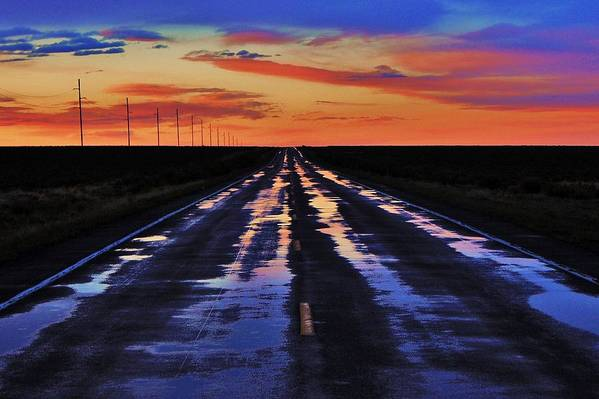 A Northern Nevada Highway Reflects The Sunset Colors After A Recent Rain Shower. Print featuring the photograph Rainy Highway by Benjamin Yeager