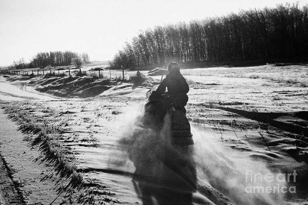 Man Art Print featuring the photograph man on snowmobile crossing frozen fields in rural Forget Saskatchewan Canada by Joe Fox