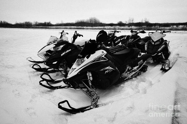 Snowmobile Art Print featuring the photograph snowmobiles parked in Kamsack Saskatchewan Canada by Joe Fox