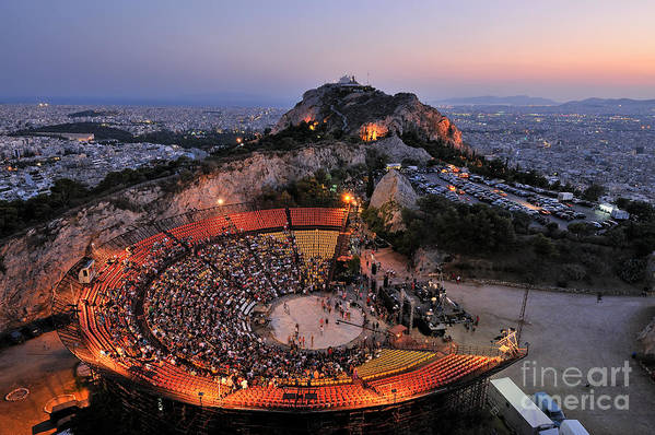 Athens; City; Capital; Attica; Attika; Attiki; Greece; Hellas; Greek; Hellenic; Europe; European; Holidays; Vacation; Travel; Trip; Voyage; Journey; Tourism; Touristic; Summer; Summertime; Lykavittos; Lykavitos; Lycabettus; Hill; Sea; View; Overview; Theater; Theatre; Open; Performance; Music; Musical; People; Photos; Photograph; Photography; Dusk; Twilight; Night; Evening; Lights Art Print featuring the photograph Lycabettus Hill by George Atsametakis