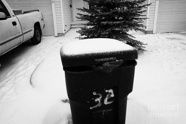 Bag Art Print featuring the photograph bag sticking out of litter waste bin covered in snow outside house in Saskatoon Saskatchewan Canada by Joe Fox