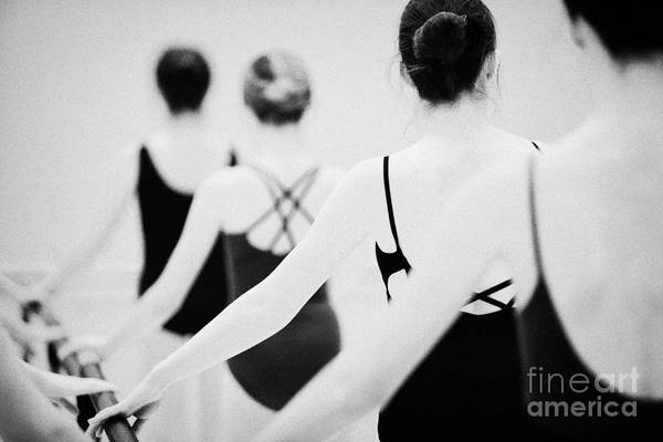 Ballet Art Print featuring the photograph Female Teenage Ballet Students Holding On To A Ballet Barre At A Ballet School In The Uk by Joe Fox