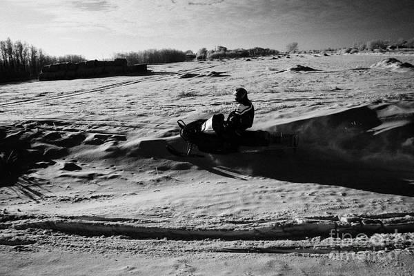Man Art Print featuring the photograph man on snowmobile crossing frozen fields in rural Forget Saskatchewan Canada by Joe Fox