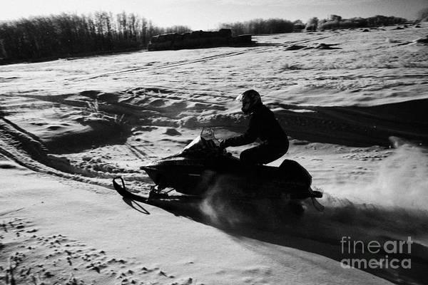 Man Art Print featuring the photograph man on snowmobile crossing frozen fields in rural Forget Saskatchewan by Joe Fox