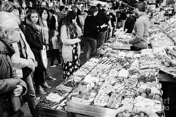 Food Art Print featuring the photograph people buying chocolates on display inside the la boqueria market in Barcelona Catalonia Spain by Joe Fox