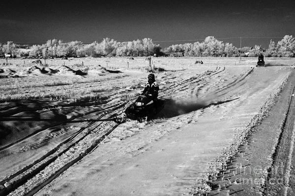 Man Print featuring the photograph two men on snowmobiles crossing frozen fields in rural Forget Saskatchewan Canada by Joe Fox