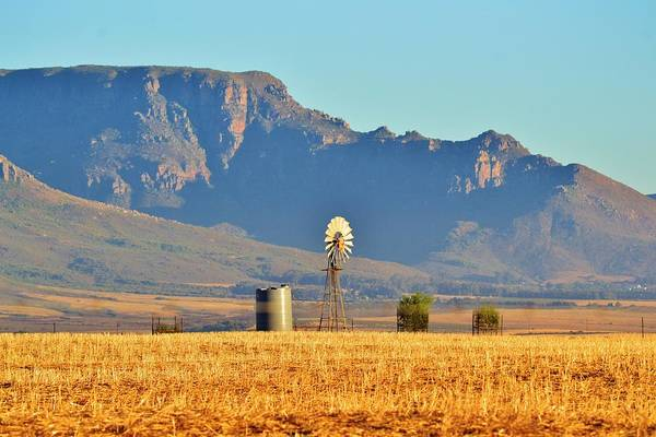 Water Pump; Windmill; Blue; Summer; Warm; Wind; Sky; Grass; Brown; Dry; Westcoast; South Africa; Landscape; Nature; Montains; Background; Decorative; Art Print featuring the photograph Water Pump Windmill by Werner Lehmann