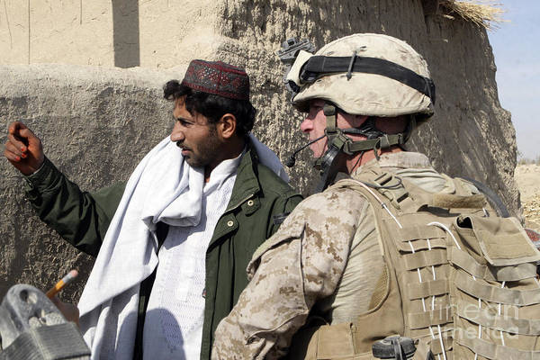 Marines Art Print featuring the photograph A Soldier Talks To A Local Villager by Stocktrek Images
