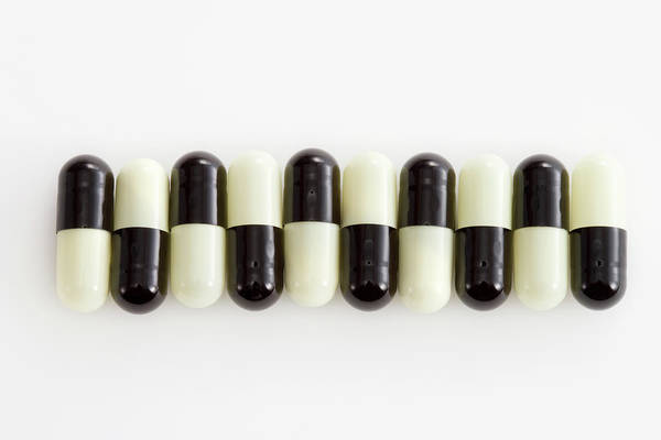 Horizontal Art Print featuring the photograph Row Of Black And White Pills by Schedivy Pictures Inc.