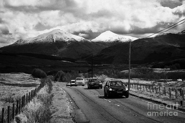 A82 Art Print featuring the photograph Traffic On A82 Trunk Road Through The Scottish Highlands With Snow Covered Mountains Ben More by Joe Fox