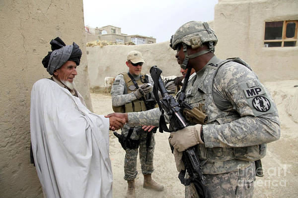 Middle East Art Print featuring the photograph U.s. Army Soldier Shakes Hands With An by Stocktrek Images