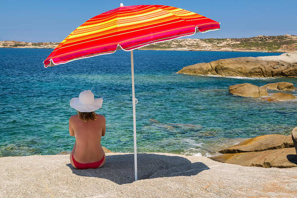 Arinella Art Print featuring the photograph Woman In Red Bikini And White Hat Under Parasol Looking Out To S by Jon Ingall