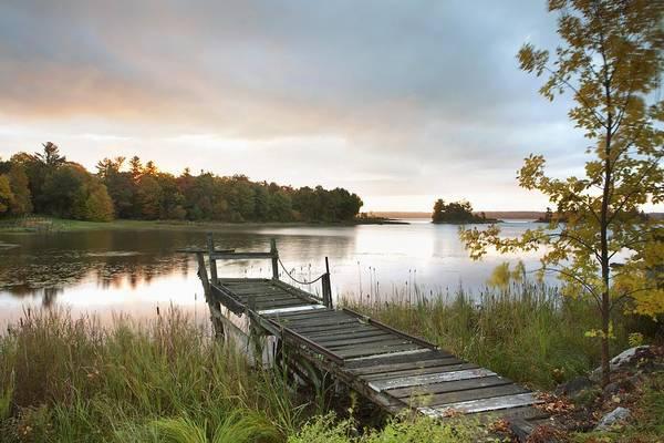 Sunrise Art Print featuring the photograph A Dock On A Lake At Sunrise Near Wawa by Susan Dykstra