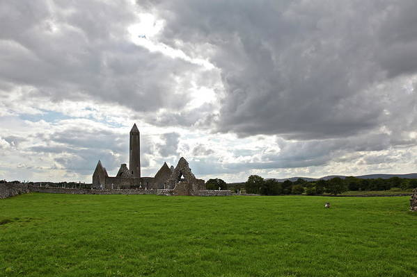 Abbey : Kilmacduagh Art Print featuring the photograph Clouds Over Kilmacduagh Abbey by Ann O Connell