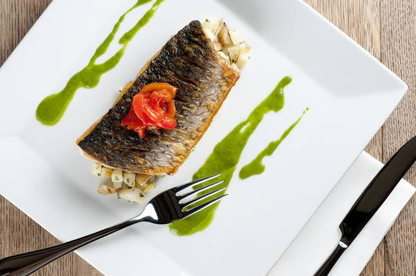 Grey Mullet Art Print featuring the photograph Grey Mullet With Watercress Sauce Presented On A Square White Plate With Cutlery And Napkin by Andy Smy