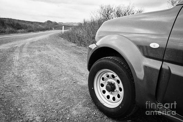 Wheel Art Print featuring the photograph Wheel Of Small 4x4 Vehicle Driving On Gravel Road Onto Main Road Reykjavik Iceland by Joe Fox